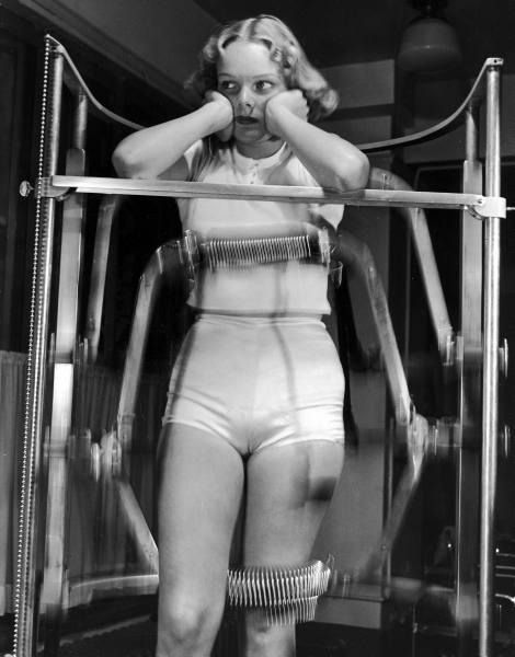 Model-Pat-Ogden-at-slenderizing-salon-enduring-the-rigors-of-the-Slendo-Massager-that-runs-rollers-up-and-down-to-electrically-rub-away-stomach-hips-and-thighs.